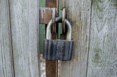 Полиняйте замок на деревянных воротах стоковое фото rf