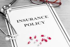 Политика медицинской страховки Стетоскоп, стекла, пилюльки на таблице Стоковое Изображение