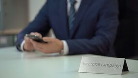 Политический консультант работая для выборной кампании, отправляя СМС на smartphone видеоматериал