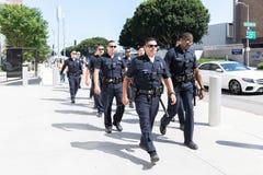 Полицейские во время семей принадлежат совместно марш Стоковые Фото