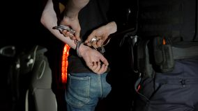 Полицейский извлекает наручники из арестованного человека