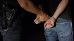 Полицейский кладет наручники на арестованный человека вечером и водит его к полицейской машине