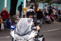 Полицейский на мотоцикле управляя вниз с улицы стоковая фотография