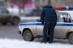 Полицейский стоит около автомобиля дорожной полиции и наблюдает пешеходные зоны дорожной полиции полиции стоковые изображения