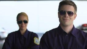 Полицейский усмехаясь к камере, женский коллега стоя позади, дружелюбные полисмены видеоматериал