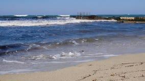 Полиэтиленовые пакеты на песчаном пляже с пристанью моря Загрязнение окружающей среды Пластиковый отход на пляже с водой брызгая  сток-видео