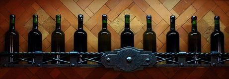 Полка погреба с темными corked бутылками вина против русой деревянной стены стоковые изображения rf