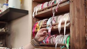 Полка с пестроткаными оборачивая лентами в магазине, рукой вытягивающ и режущ ее сток-видео