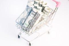 Полная вагонетка покупок с банкнотами доллара на белой предпосылке изолировано Концепция защиты интересов потребителя и денег Стоковая Фотография
