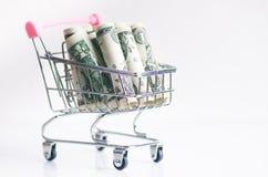 Полная вагонетка покупок с банкнотами доллара на белой предпосылке изолировано Концепция защиты интересов потребителя и денег Стоковая Фотография RF