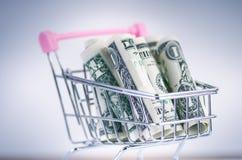 Полная вагонетка покупок с банкнотами доллара на белой предпосылке изолировано Концепция защиты интересов потребителя и денег Стоковое Изображение RF