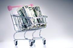 Полная вагонетка покупок с банкнотами доллара на белой предпосылке изолировано Концепция защиты интересов потребителя и денег Стоковое фото RF
