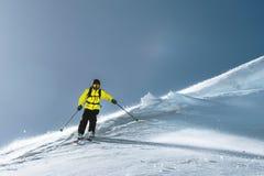 Полная длина катания на лыжах на свежем порошке снега Профессиональный лыжник вне следа на солнечный день стоковые фотографии rf