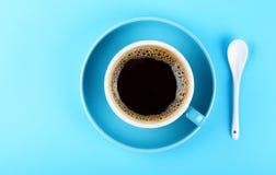 Полная чашка черного кофе и поддонника над синью стоковая фотография