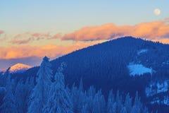 Полнолуние поднимает среди красочных облаков Стоковые Изображения