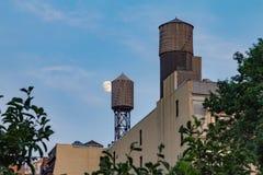 Полнолуние поднимая за водонапорной башней на крыше зданий внутри Стоковое фото RF