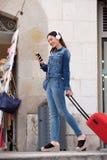 Полнометражная женщина идя снаружи с багажом и наушниками Стоковое Фото