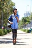 Полнометражная привлекательная молодая женщина идя снаружи с сотовым телефоном и сумкой Стоковые Фото
