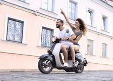 Полнометражный взгляд со стороны счастливого катания пар на ретро мотоцилк стоковое фото