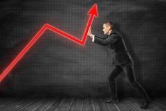 Полнометражный вид сбокуый бизнесмена нажимая красную стрелку диаграммы идя вверх около черной диаграмм-управляемой стены стоковая фотография rf