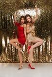Полнометражный портрет 2 веселых девушек в сияющих платьях Стоковые Фото