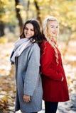 Полнометражный портрет молодой женщины представляя с подругой в парке осени Стоковое Изображение RF