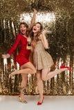 Полнометражный портрет 2 радостных девушек в сияющих платьях Стоковое фото RF