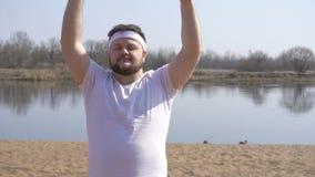 Полностью бородатый человек в белой футболке приниманнсяый за метод йоги на природе на фоне реки, экземпляре видеоматериал