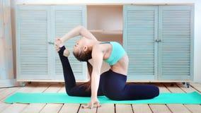 Полностью снятая женщина йоги протягивая тазобедренные мышцы подколенного сухожилия ноги практикуя представление голубя на циновк акции видеоматериалы