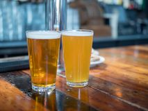 Полные стекла пинты эля и золотых пив сидя на счетчике бара Стоковое Фото