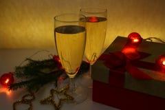 Полные стекла шампанского на желтой предпосылке с подарком и украшений для рождества Стоковые Фотографии RF