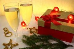 Полные стекла шампанского на желтой предпосылке с подарком и украшений для рождества Стоковые Изображения
