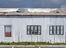 полный конец рамки вверх затрапезного старого разрушанного здания волнистого железа с с закрытым покрашенным над залатанными окна стоковая фотография