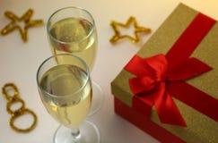 2 полных стекла шампанского на желтой предпосылке с подарком Стоковое Изображение RF