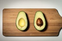 Половина отрезка авокадоа на разделочной доске стоковое изображение rf
