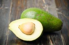 Половина плодоовощ авокадоа на деревянной предпосылке Стоковые Изображения