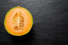 Половина плодоовощ дыни Hami на черной каменной поверхности предпосылки с открытым космосом стоковая фотография rf
