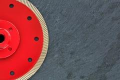 Половина режущего диска диаманта красна с продетой нитку гайкой на предпосылке серого гранита стоковые изображения rf