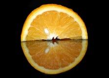 Половина сочного апельсина в отражении стоковые фотографии rf