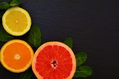 Половина сочных зрелых grapfruit, апельсина и лимона с листьями мяты Стоковое Фото