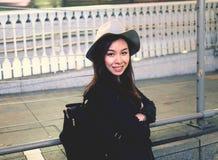 Половинная длина молодой красивой азиатской женщины битника в смотреть города усмехаясь в камере стоковое изображение