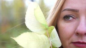 Половинная сторона красивой белокурой девушки с лист осени в лесе в цветах падения замедленное движение 4k 3840x2160 сток-видео