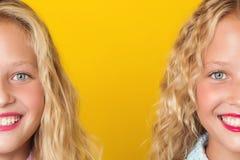 Половинная сторона 2 teenages дублирует конец-вверх, изолированный на желтой предпосылке Стоковое Фото