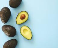 Половины авокадоа и все на голубой предпосылке Стоковые Фотографии RF