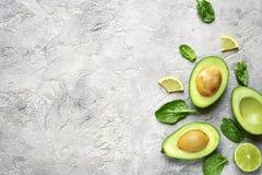 Половины авокадоа с кусками известки и листьями шпината младенца верхняя часть соперничает Стоковые Фотографии RF