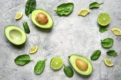 Половины авокадоа с кусками известки и листьями шпината младенца верхняя часть соперничает Стоковые Изображения