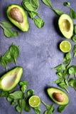 Половины авокадоа с шпинатом младенца выходят и известка Взгляд сверху с c Стоковые Изображения RF