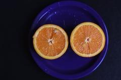 2 половины апельсина на голубой плите Подготавливайте для juicing Стоковые Изображения RF