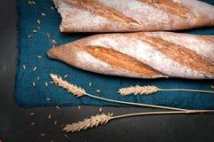 Половины багета лежат на темной салфетке на черной поверхности Рядом колоски пшеницы стоковая фотография rf