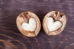 2 половины грецкого ореха в форме сердца лежат на покрашенной темноте Стоковое Изображение RF